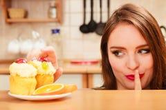 Frau, die den Kuchen zeigt ruhiges Zeichen isst gluttony stockfoto