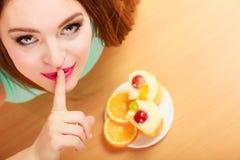 Frau, die den Kuchen zeigt ruhiges Zeichen isst gluttony stockfotos