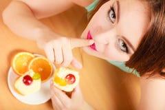 Frau, die den Kuchen zeigt ruhiges Zeichen isst gluttony stockbilder