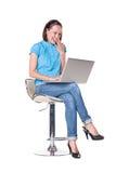 Frau, die den Laptop und das Lachen betrachtet Stockbilder