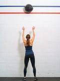 Frau, die den Medizinball an der Turnhalle wirft Lizenzfreies Stockbild