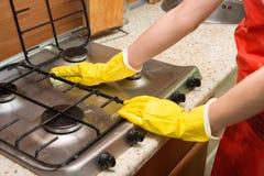Frau, die den Ofen in der Küche säubert Haushaltungskonzept stockfoto