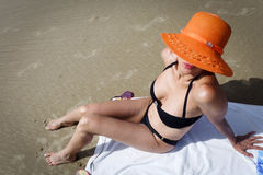 Frau, die den orange Hut sitzt auf Strand trägt Stockbild