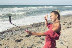 Frau, die den Ozean bereitsteht und ein selfie nimmt Lizenzfreie Stockfotos
