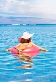 Frau, die in den Ozean sich entspannt und schwimmt Lizenzfreies Stockfoto