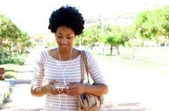 Frau, die in den Park hört Musik am Telefon geht lizenzfreies stockfoto