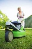 Frau, die den Rasen im Garten mäht Lizenzfreie Stockbilder