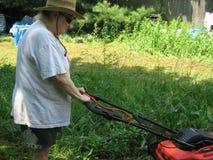 Frau, die den Rasen mäht Stockbild