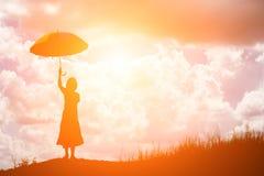 Frau, die den Regenschirm allein steht am Feld während des beauti hält Lizenzfreie Stockfotografie
