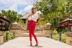 Frau, die in den roten Hosen und in den hohen Absätzen aufwirft Lizenzfreie Stockfotos