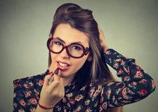 Frau, die den roten Lippenstift schaut in Spiegel einsetzt Make-up nachts werden fertig bevor dem Gehen zur Partei Lizenzfreie Stockfotografie