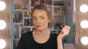 Frau, die den roten Lippenstift schaut in Spiegel einsetzt Make-up nachts werden fertig bevor dem Gehen zur Partei Lizenzfreies Stockbild