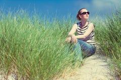 Frau, die in den Sanddünen unter der hohen Grasentspannung, die Ansicht genießend am sonnigen Tag sitzt Lizenzfreie Stockbilder