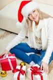 Frau, die den Sankt-Hut sitzt auf dem Fußboden trägt Stockfotos