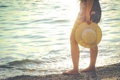 Frau, die den schönen Sonnenuntergang auf dem Strand genießt stockbilder