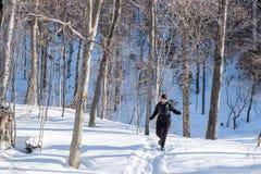 Frau, die in den Schnee läuft Stockbild