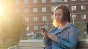 Frau, die den Smartphone sitzt auf Bank in der Stadt verwendet stock footage