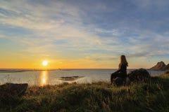 Frau, die den Sonnenaufgang, Ansicht von Vaeroy-Insel, Lofoten, Norwegen aufpasst Lizenzfreie Stockfotos
