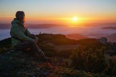 Frau, die den Sonnenaufgang in den Bergen genießt Stockbild