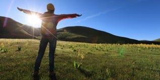 Frau, die in den Sonnenaufgangbergen wandert Lizenzfreie Stockbilder