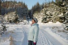 Frau, die den Sonnenschein im Wald im Winter genießt Lizenzfreie Stockbilder