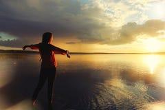 Frau, die den Sonnenuntergang nach dem Regen bereitsteht den See aufpasst Stockfotos