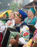 Frau, die den Spaß singt und spielt das Akkordeon hat Stockfotografie