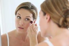 Frau, die den Spiegel anwendet einen Abdeckstift betrachtet Lizenzfreie Stockfotos