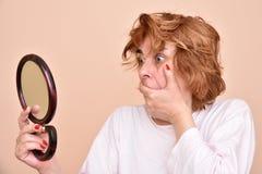 Frau, die den Spiegel betrachtet stockbild