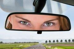 Frau, die den Spiegel eines Autos betrachtet lizenzfreies stockfoto
