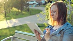 Frau, die den Tablet-Computer sitzt auf Bank in der Stadt verwendet stock footage