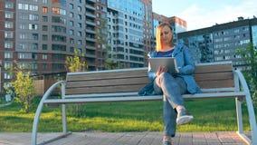 Frau, die den Tablet-Computer sitzt auf Bank in der Stadt verwendet stock video