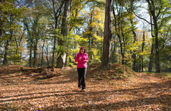 Frau, die in den Wald läuft Lizenzfreie Stockfotografie