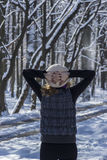 Frau, die den Wald am Wintertag erwägt Stockfotografie