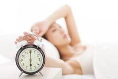 Frau, die den Wecker auf dem Bett abstellt lizenzfreie stockfotografie