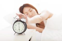 Frau, die den Wecker auf dem Bett abstellt lizenzfreie stockbilder
