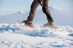 Frau, die in den Winterkarpatenbergen snowshoeing ist Lizenzfreie Stockfotografie