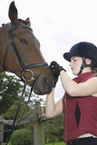 Frau, die den Zaum des Pferds festzieht lizenzfreie stockfotografie