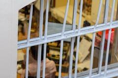 Frau, die an der Büroansicht durch Gitter arbeitet Leute werden betont, weil sie in Arbeitsplatzüberstunden eingeschlossen werden stockfoto