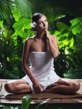 Frau, die in der Badekurorttropenumwelt meditiert Lizenzfreie Stockfotos