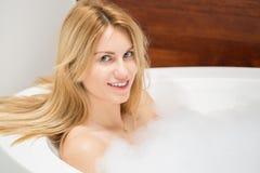 Frau, die in der Badewanne sich entspannt lizenzfreies stockbild