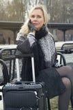 Frau, die an der Bahnstation mit ihrem Koffer sitzt Lizenzfreie Stockbilder