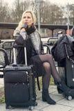 Frau, die an der Bahnstation mit ihrem Koffer sitzt Stockfotografie