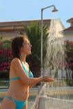 Frau, die in der blauen Badeanzugnehmendusche trägt Stockbild