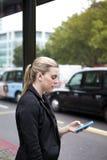 Frau, die an der Bushaltestelle mit Handy in London wartet Lizenzfreie Stockfotografie