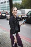 Frau, die an der Bushaltestelle mit Handy in London wartet Stockbilder