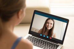 Frau, die der Freundin Videoanruf auf Laptop macht stockfotografie