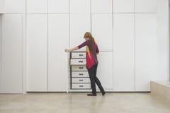 Frau, die in der Garderobe in der leeren Wohnung schaut Stockbilder