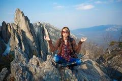 Frau, die an der Gebirgsspitze meditiert lizenzfreie stockfotografie