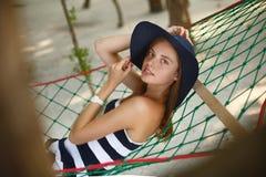 Frau, die in der Hängematte auf tropischem Strand im Schatten, heißer sonniger Tag sich entspannt Mädchen schaut zur Kamera mit L Lizenzfreie Stockbilder